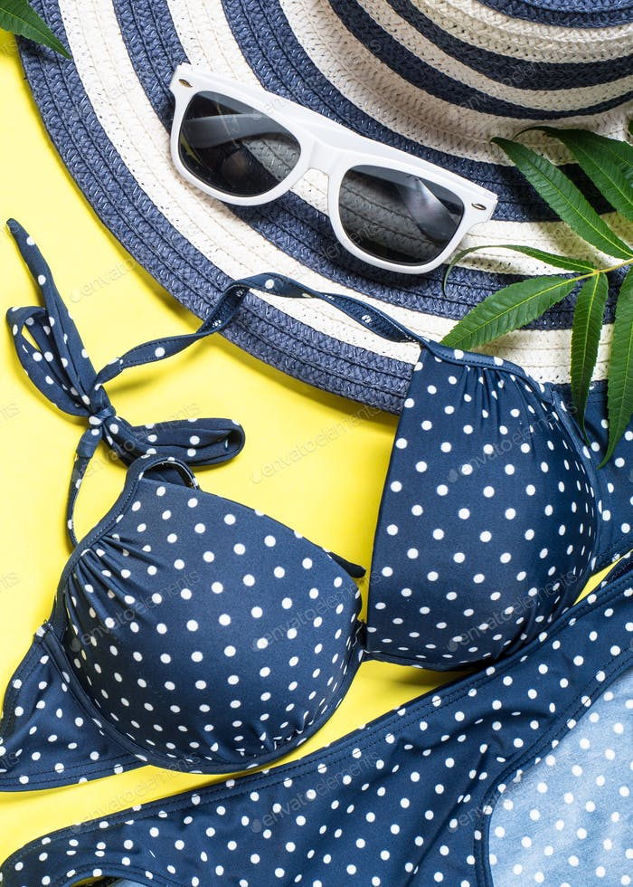 Woman summer beach cloth set - hat, swimsuit and sunglasses on yellow top view.
