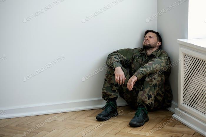Depressiver Armeemann in Uniform sitzt in einer Ecke eines leeren ro