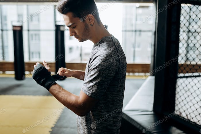 Guy dressed in the grey t-shirt wraps a hand bandage on his hand in the boxing gym