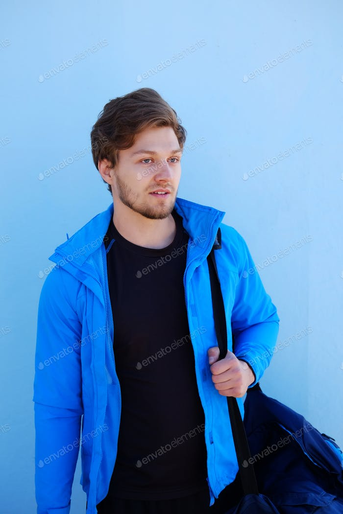 Attractive bearded positive sporty male in a blue jacket.