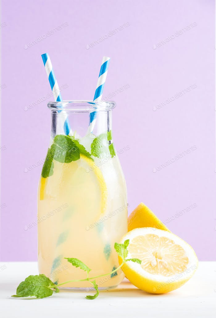 Bottle of homemade lemonade with mint, ice, lemons, paper straws and pastel lilac background