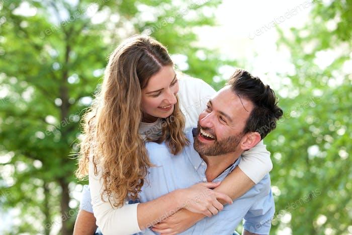 Laughing boyfriend carrying girlfriend outside in park