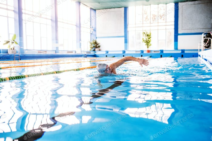 Senior man swimming in an indoor swimming pool.