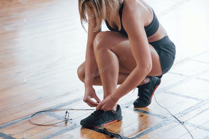 Girl preparing for the training. Sitting on the floor of modern gym