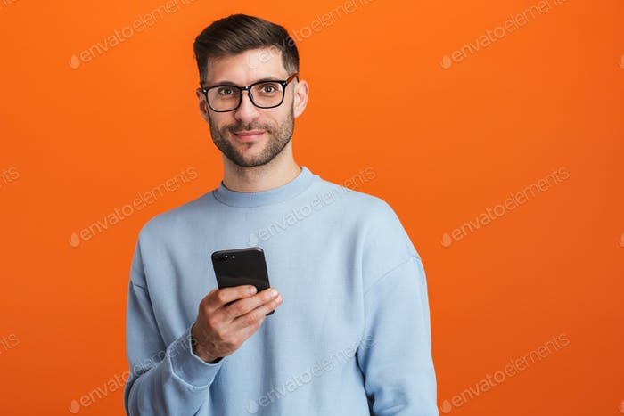 Image of young bearded handsome man wearing eyeglasses holding cellphone