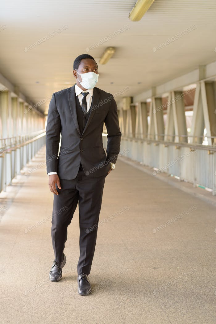 Full body shot of African businessman with mask walking at the footbridge