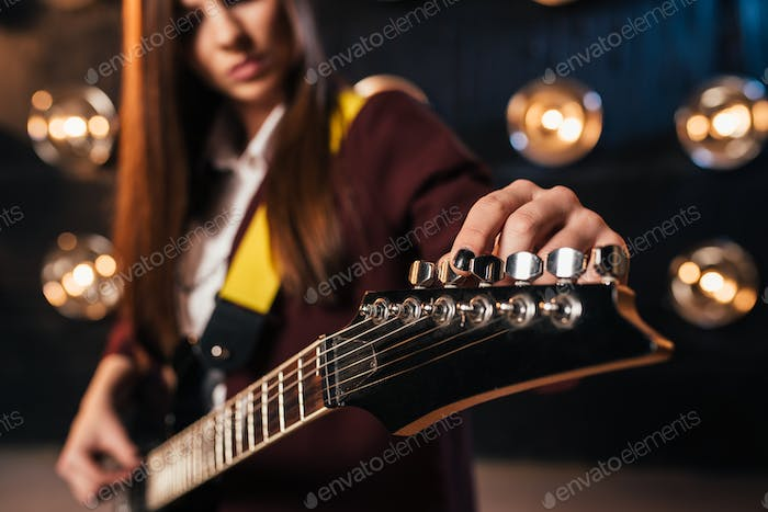 Female rock guitarist in suit tunes the guitar