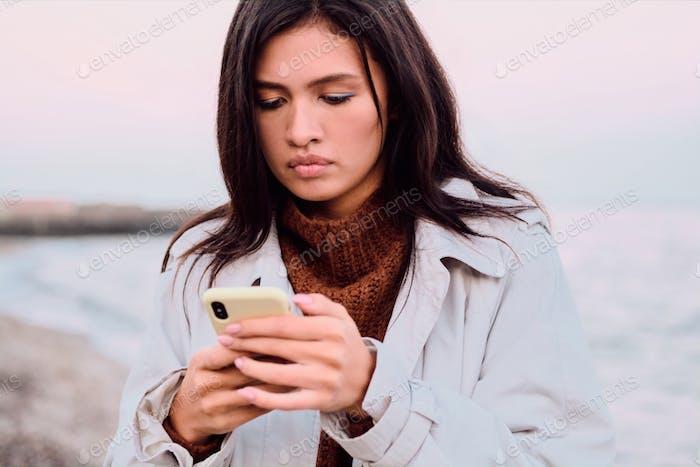 Beautiful pensive Asian brunette girl thoughtfully using cellphone on sunset beach