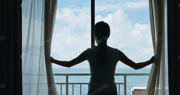 Frau öffnen Sie den Vorhang