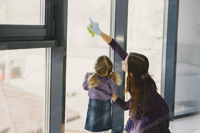 Hija y madre limpiando ventana juntos
