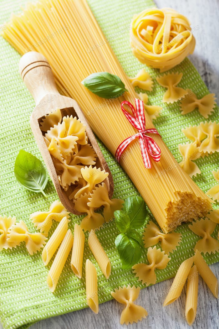 raw pasta spaghetti farfalle penne, tomatoes. italian cuisine