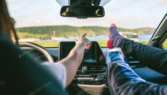 Young couple traveling by car feet up barefoot