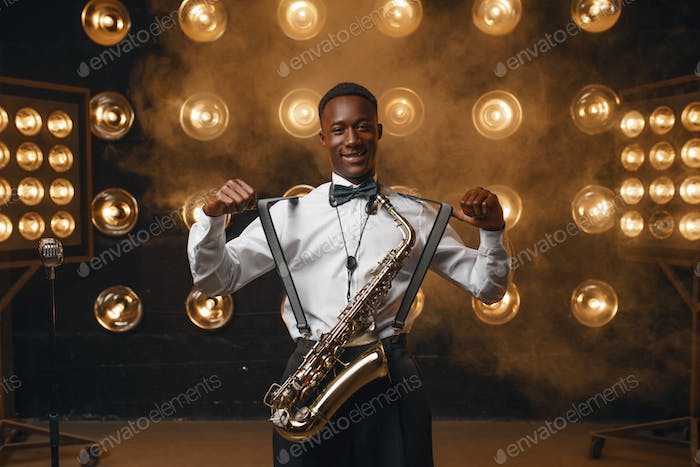 Smiling jazz performer with saxophone on stage