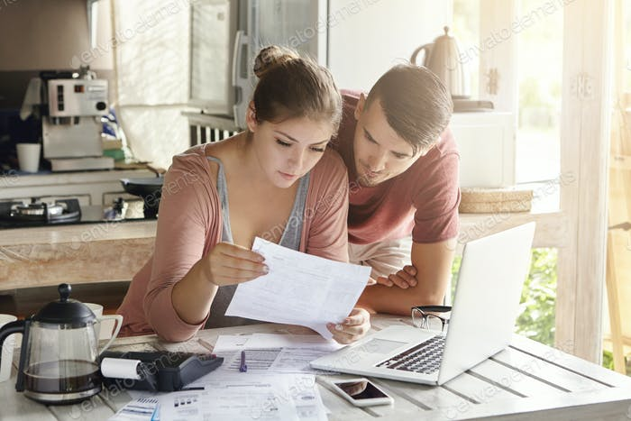 Young couple managing finances, reviewing their bank accounts using laptop computer and calculator a