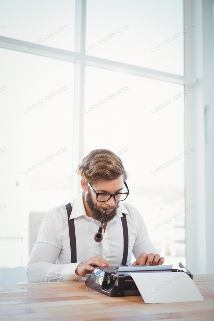 Hipster wearing eye glasses smoking pipe while working on typewriter at desk in office