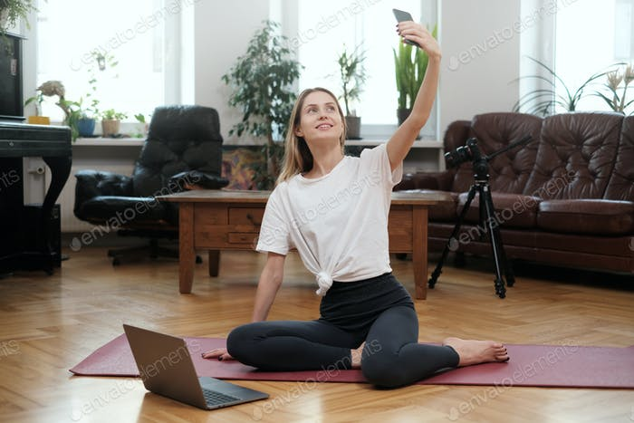 Stilvolle Frau schießt sich mit ihrem Handy im modernen Zimmer
