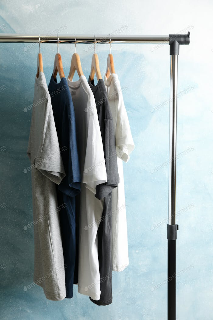 Rack with blank t-shirts on blue background. Black Friday sale