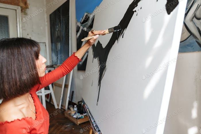 Portrait of young woman using painting tools while drawing in studio