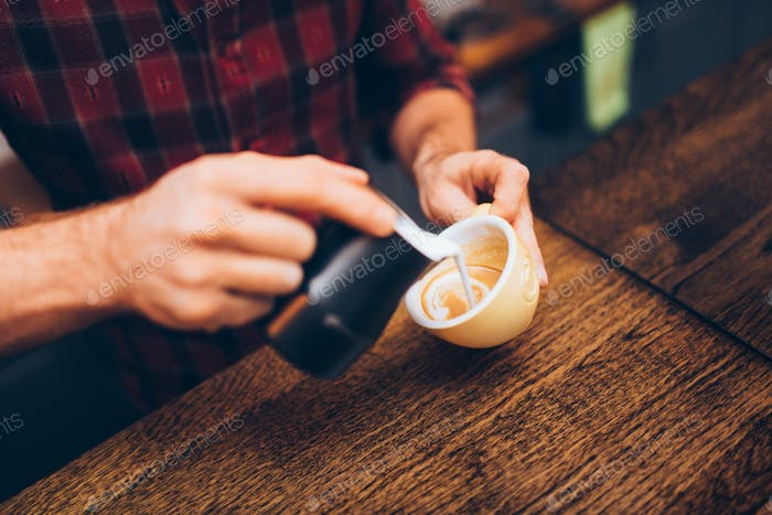 Professional barista pouring latte foam over coffee,