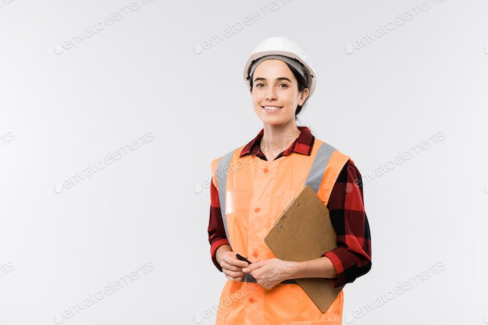 Successful young female engineer in protective helmet and orange jacket