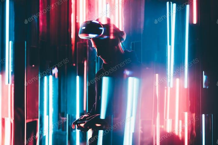 Mann mit VR-Headset in dunklem Innenraum beleuchtet Neonlicht.