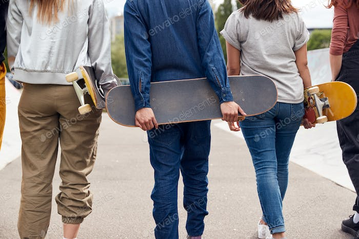 Rear View Of Female Friends With Skateboards Walking Through Urban Skate Park