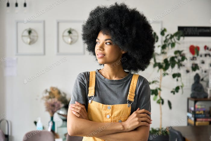 Young confident african woman entrepreneur standing in cafe with arms crossed.