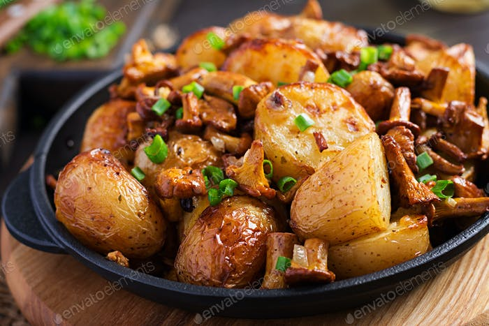 Baked potatoes with garlic, herbs and fried chanterelles in a cast iron skillet.