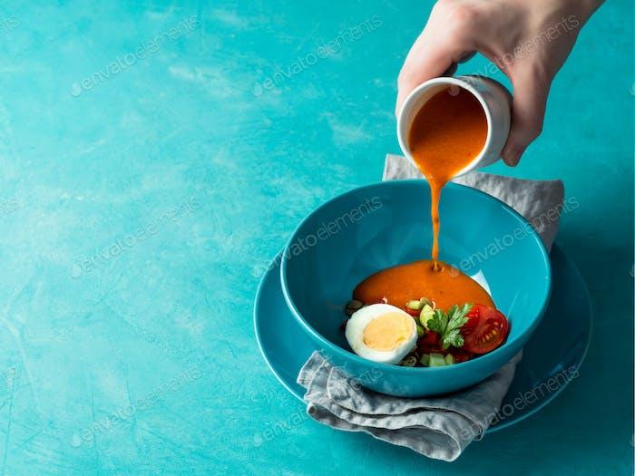 Handgießen von Gaspacho Suppe in Schüssel