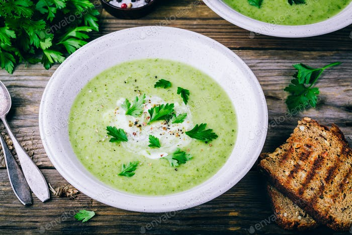 bowl of green zucchini cream soup with fresh parsley