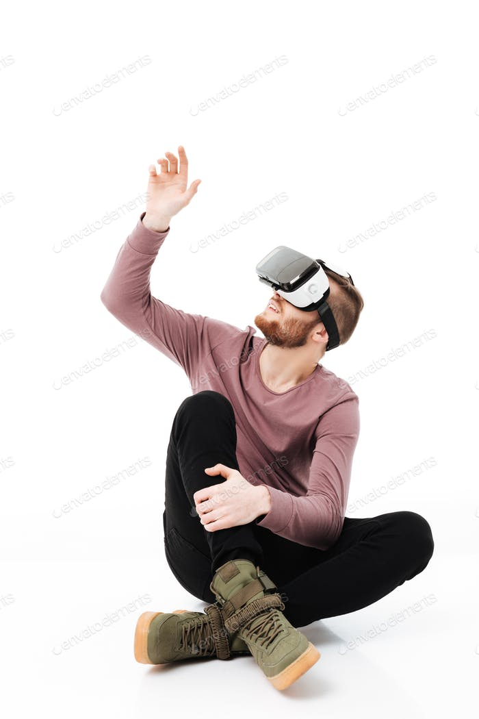 Young man sitting in studio and playing with virtual reality glasses over white background