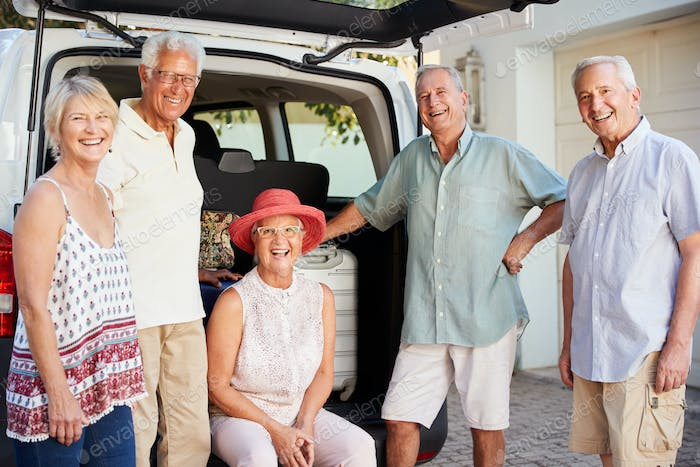 Portrait Of Senior Friends Loading Luggage Into Trunk Of Car About To Leave For Vacation