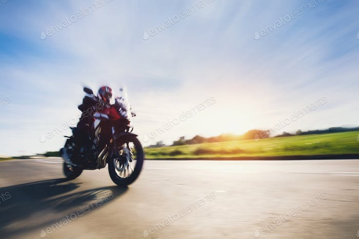 Drive a motorbike. Fast motorcycle in motion on asphalt road.