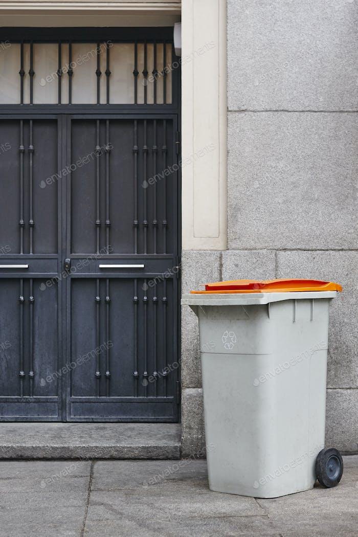 Mülltonne an einem städtischen Gebäude Eingangstür. Saubere Umwelt
