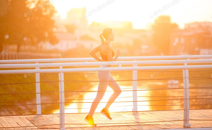 Young woman running on bridge early in morning, sun flare effect