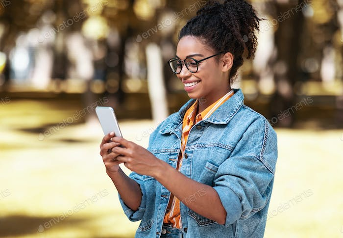 Cheerful African Millennial Girl Using Phone Walking In Park Outdoors