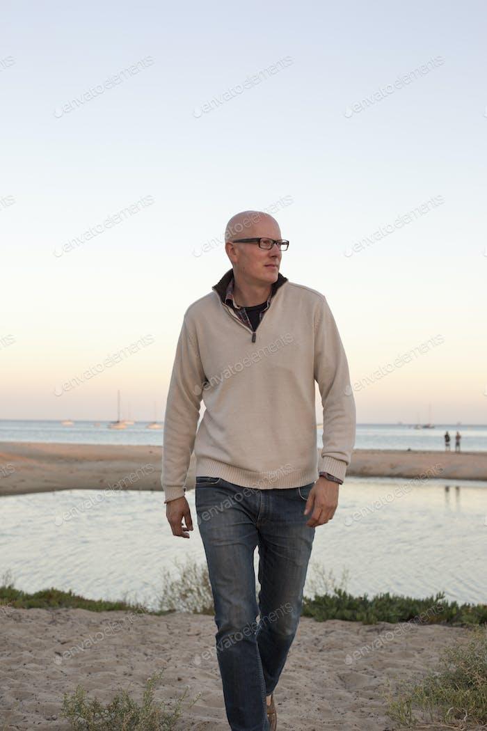 Bald man walking on a sandy beach by the ocean.