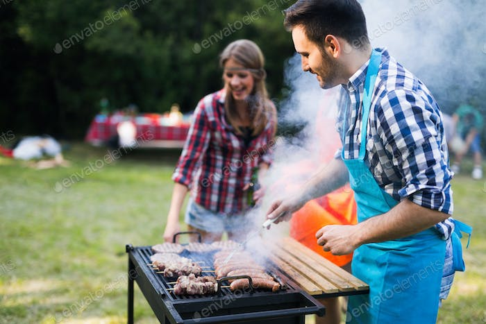 Young happy people grilling outdoors and smiling