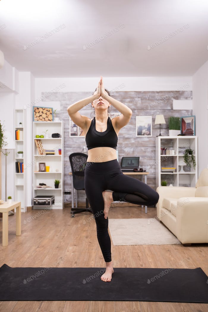 Young caucasian woman practicing tree yoga pose