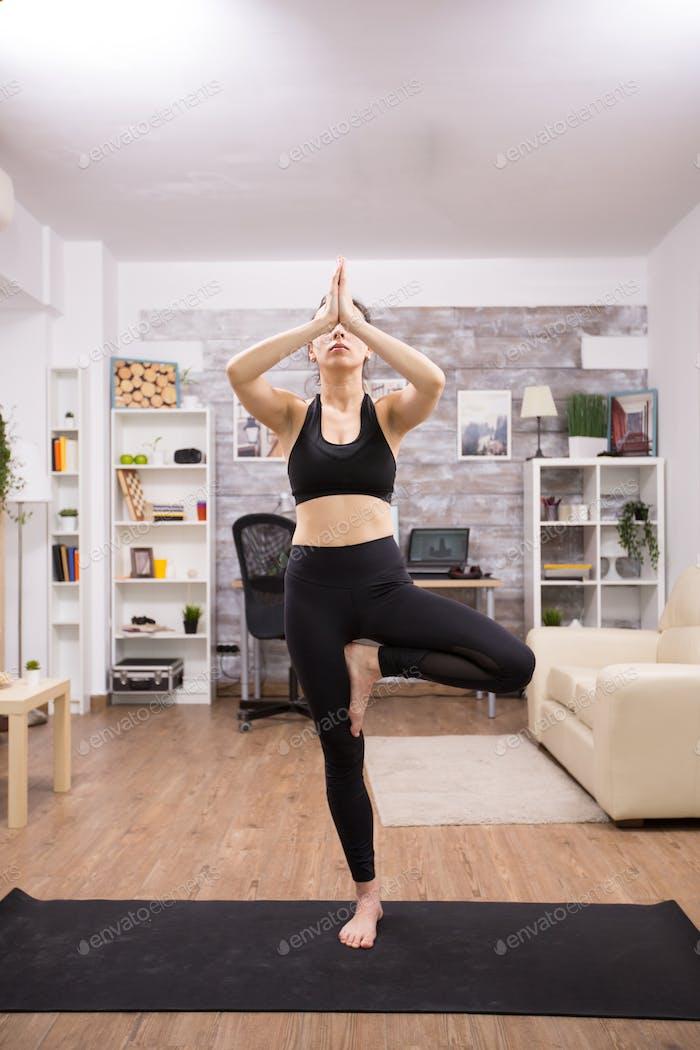 Junge kaukasische Frau Üben Baum Yoga Pose