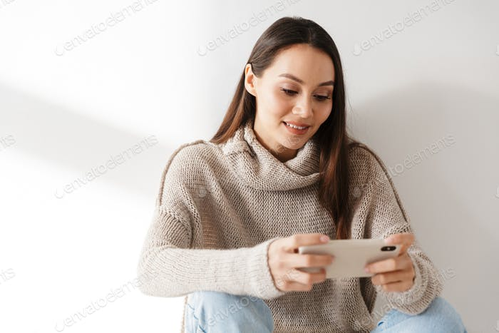 Image of asian woman sitting and playing video game on smartphone