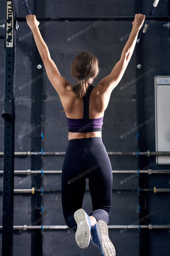Young Woman Doing Pull Ups in Gym