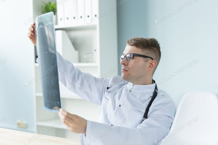 Healthcare and medical concept - Handsome bearded doctor checking X-ray image