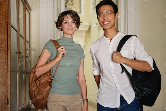 Two young attractive international students with backpacks happily looking in camera