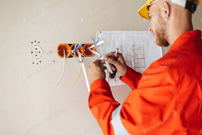 Close up builder in orange work clothes and yellow hardhat worki