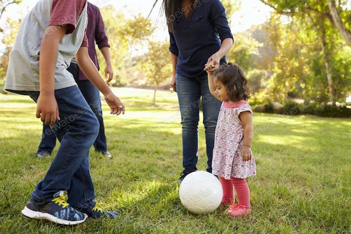 Junge gemischte Rasse Familie spielen mit Ball in einem Park, Ernte