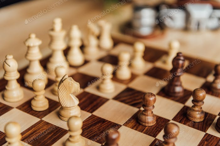 Detail view of chess set on chessboard. Selective focus on white chess horse figure