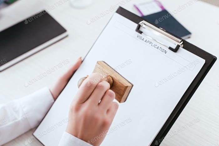 enfoque selectivo de la abogada con sello en la mano sosteniendo portapapeles con solicitud de visado
