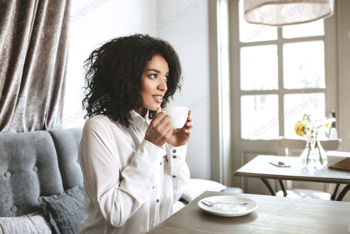 Beautiful African American girl sitting in restaurant with cup in hands