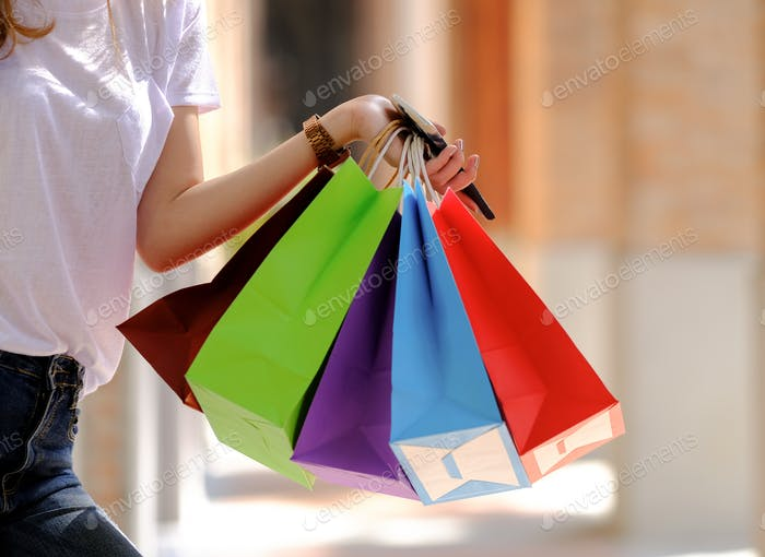 Young girl shopper hold several shopping bags on hand.